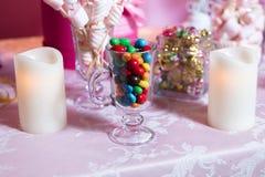 五颜六色的糖果 多色的甜点 在玻璃的色的糖果 圆的巧克力是非常五颜六色的 蜡烛 免版税图库摄影