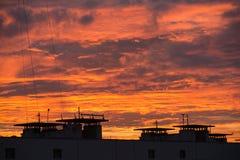 五颜六色的红色天空自然本底在与街道屋顶的日落时间 库存图片