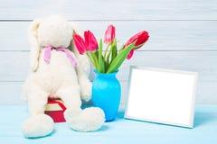 五颜六色的红色春天郁金香在精密蓝色花瓶、空白的照片框架和被充塞的玩具兔宝宝开花在轻的木背景作为greetin 免版税库存图片