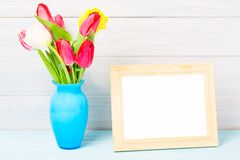 五颜六色的红色春天郁金香在精密蓝色花瓶和空白的照片框架开花在轻的木背景当贺卡 Mothersday 库存图片