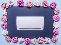 五颜六色的纸玫瑰框架,计划在与信封中间顶视图关闭的黑暗的背景地方文本 免版税库存照片