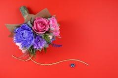 五颜六色的纸花花束和在红色背景的小蓝色心脏作为明信片,邀请信的一个背景和 库存照片