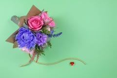 五颜六色的纸花花束和在绿色背景的小红色心脏作为明信片的的邀请信一个背景 库存照片