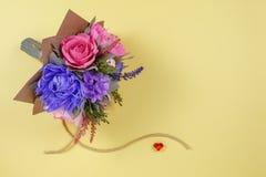 五颜六色的纸花花束和在黄色背景的小红色心脏作为明信片的,邀请信a一个背景 图库摄影