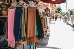 五颜六色的纺织品围巾的汇集在户外挂衣架的在显示在摊贩` s摊,室外购物 库存图片