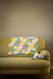 五颜六色的羊毛席子、毛线和钩针编织针在长沙发 免版税库存图片