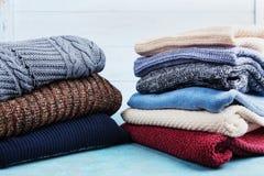 五颜六色的羊毛毛线衣和被编织的冬天在蓝色木背景穿衣 库存图片