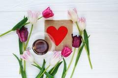 五颜六色的美丽的郁金香和咖啡在中心在白色木桌上 华伦泰,春天背景 免版税库存照片