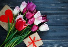 五颜六色的美丽的郁金香和礼物盒在灰色木桌上 华伦泰,春天背景 花卉嘲笑与copyspace 免版税库存照片