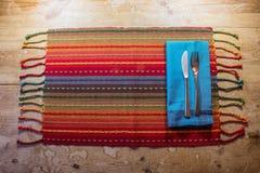 五颜六色的美国西南启发了晚餐在一张土气木桌上的餐位餐具 免版税图库摄影
