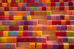 五颜六色的肥皂立方体用与大写字母的不同的颜色。 免版税库存照片