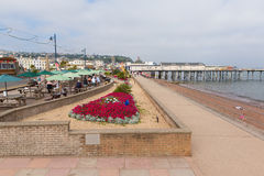 五颜六色的花和假日游客Teignmouth码头和海滩德文郡英国英国 免版税图库摄影