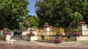 五颜六色的花床和石喷泉在达拉斯树木园和植物园的入口 库存图片