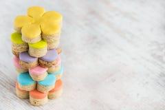五颜六色的花形式自创方旦糖盖了在白色木背景的曲奇饼 库存图片