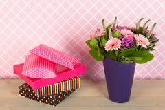五颜六色的花束在蓝色花瓶和被包裹的礼物开花 免版税库存照片