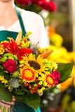 五颜六色的花束开花拿着花市场的卖花人 库存图片