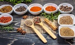 五颜六色的芳香印地安香料和草本在一个老橡木木深刻的蓝色板 库存图片