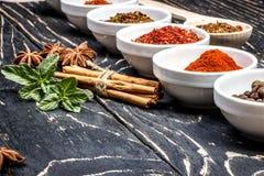五颜六色的芳香印地安香料和草本在一个老橡木木深刻的蓝色板 免版税库存图片