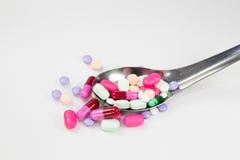 五颜六色的药片和胶囊在匙子在白色背景中 免版税库存图片