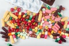 五颜六色的药片在白色背景喷溅 不同的片剂和胶囊堆混合疗法药物 免版税图库摄影