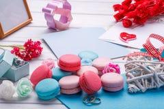 五颜六色的蛋白杏仁饼干 婚礼主题 婚姻白色的背景明亮的环形 与信封的明信片 免版税图库摄影