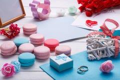 五颜六色的蛋白杏仁饼干 婚礼主题 婚姻白色的背景明亮的环形 与信封的明信片 库存图片