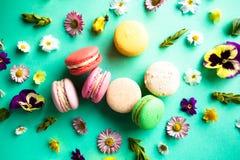 五颜六色的蛋白杏仁饼干和花 免版税库存照片