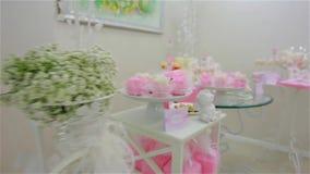 五颜六色的蛋白甜饼和蛋糕在不同的桌上 股票录像