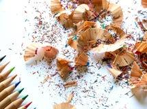 五颜六色的蜡笔和铅笔削片在白色背景 图库摄影