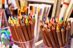 五颜六色的蜡笔被安置入杯子在学生` s桌 免版税库存照片