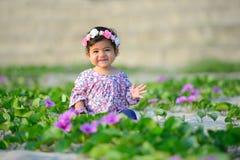 戴五颜六色的衣服和花帽子的微笑的女婴是playin 库存图片