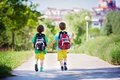 五颜六色的衣裳和背包的,走的awa两个可爱的男孩 免版税库存照片