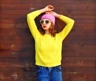 五颜六色的衣裳的画象时尚凉快的女孩在穿桃红色帽子黄色毛线衣的木背景 库存照片