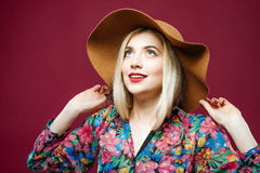 五颜六色的衬衣和帽子的微笑的妇女在桃红色背景摆在 与长的头发的惊人的白肤金发的模型在演播室 免版税库存图片