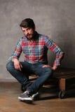 五颜六色的衬衣的有胡子的人坐一个木板 库存照片