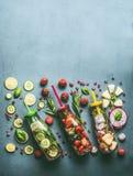 五颜六色的被灌输的水品种在瓶的用果子莓果、黄瓜、草本和饮料秸杆与成份在桌,上面上 图库摄影