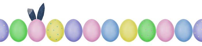五颜六色的被绘的复活节彩蛋接近的照片与连续被安排的蛋壳纹理的 与牛仔布纺织品兔宝宝耳朵的一个鸡蛋 免版税库存照片