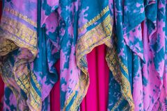 五颜六色的被装饰的重叠的与金子黄色被绣的设计- boho或吉普赛神色的织品和绿松石背景在桃红色的 库存图片