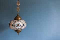 五颜六色的装饰垂悬的光对有拷贝空间的蓝色墙壁 免版税图库摄影