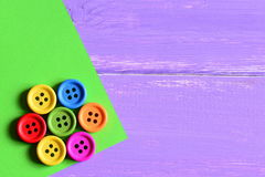 五颜六色的装饰木圆的按钮 在绿皮书板料的抽象花 与拷贝空的空间的木背景文本的 图库摄影