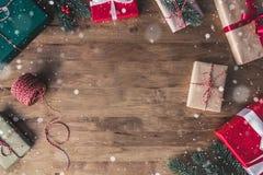 五颜六色的装饰的礼物盒顶视图在一张木桌上的与下跌的雪作用 免版税库存图片