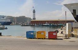 五颜六色的金属容器连续在江边的分开的无用单元收集的巴塞罗那旧港口的  免版税库存照片