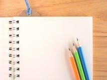 五颜六色的铅笔和空白的book's在木书桌上的paer 库存图片