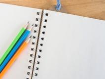 五颜六色的铅笔和空白的book's在木书桌上的paer 图库摄影