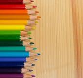 五颜六色的铅笔彩虹秩序行在木桌上的 图库摄影