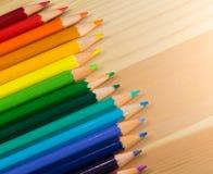 五颜六色的铅笔彩虹秩序行在木桌上的 免版税库存照片