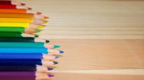 五颜六色的铅笔彩虹秩序行在木桌上的 库存图片