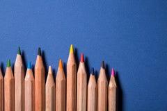 五颜六色的铅笔行在蓝色背景的 库存图片
