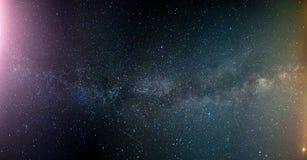 五颜六色的银河和黄灯 与小山的满天星斗的天空在夏天 美丽的宇宙 空间背景 库存照片