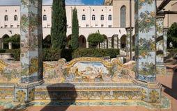 五颜六色的铺磁砖的柱子在圣基娅拉教堂修道院的修道院庭院里通过圣基娅拉教堂,那不勒斯意大利 免版税库存照片